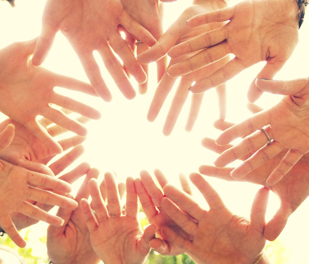 A close-up of many hands in a circle clasping together in a sign of unity.